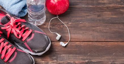 Sport equipment. Sneakers, water and earphones on wooden background