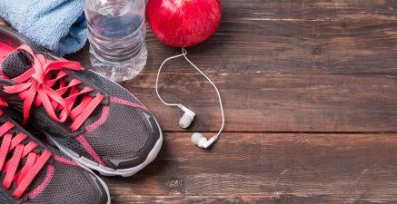 Sport equipment. Sneakers, water and earphones on wooden background